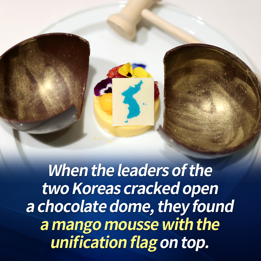 When the leaders of the two Koreas cracked open a chocolate dome, they found a mango mousse with the unification flag on top.